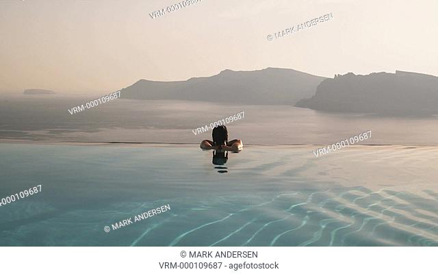 woman in an infinity pool overlooking the Mediterranean