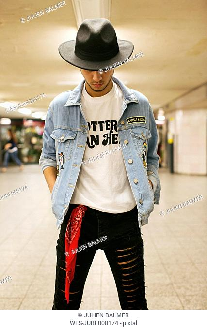 Fashionable young man wearing hat and jeans jacket