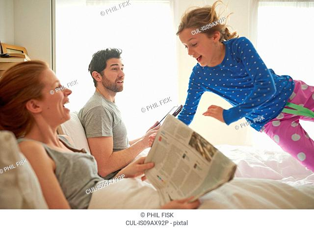 Mid adult couple reading broadsheet whilst daughter leaps on bed