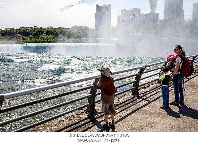 A family consisting of a 6 year old Japanese American boy, 4 year old Japanese American boy, a Japanese American mother and her 6 month old baby look at Niagara...
