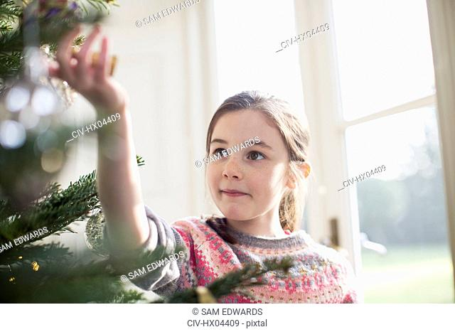 Curious girl touching ornament on Christmas tree