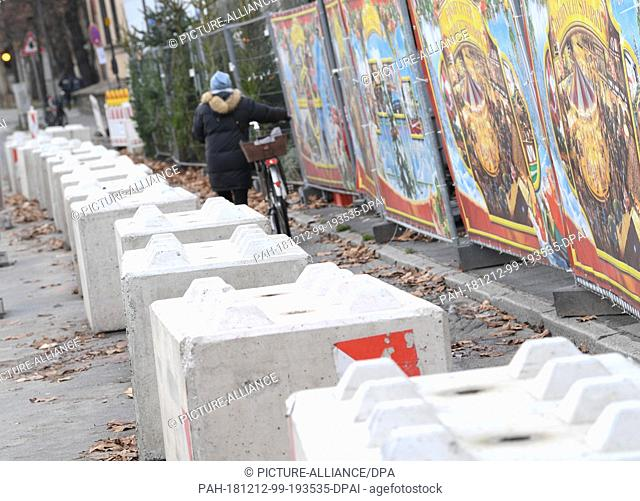 12 December 2018, Hessen, Frankfurt/Main: Concrete barriers are placed at the edge of Frankfurt's Christmas market on a street