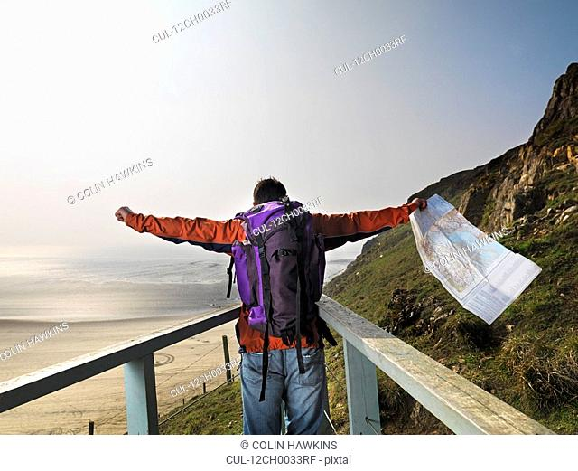 man hiking on cliff edge