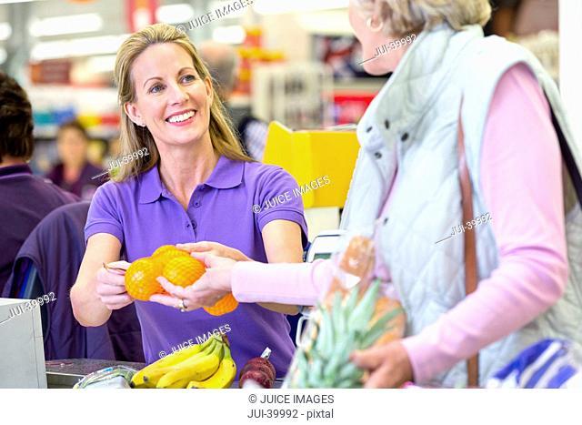 Cashier Serving Customer At Supermarket Checkout