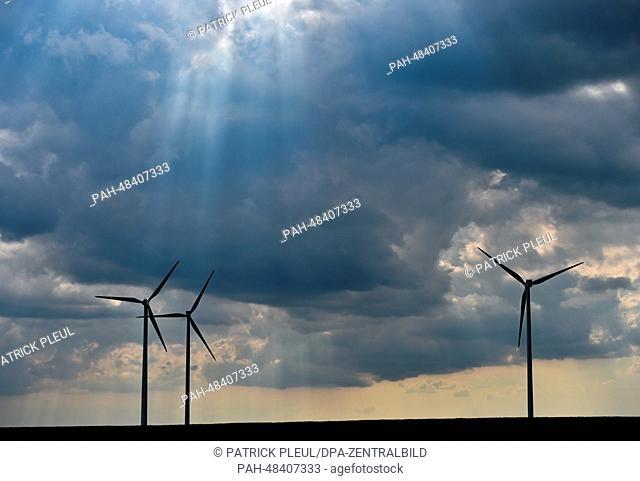 The sun breaks through rain clouds which darken the sky above wind turbines on a field near Sieversdorf, Germany, 07 May 2014