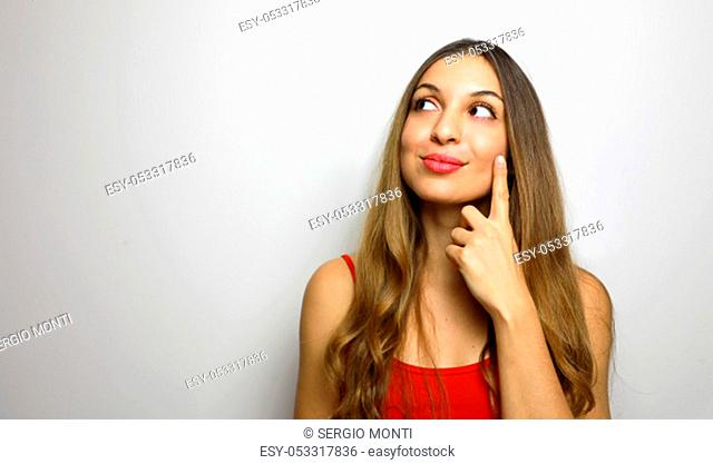 I have great idea! Studio shot of attractive female moving fingers near cheek as if making up plan in mind, smiling while looking happy aside