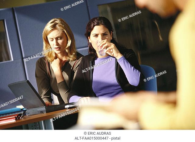 Two female office workers using laptop, one drinking glass of water