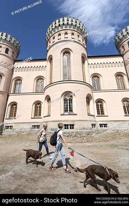 03 August 2020, Mecklenburg-Western Pomerania, Binz: Two women run with their dogs past the towers of the Granitz hunting lodge