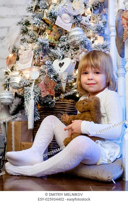 Happy pretty girl with toy bear sits near a Christmas tree in the room