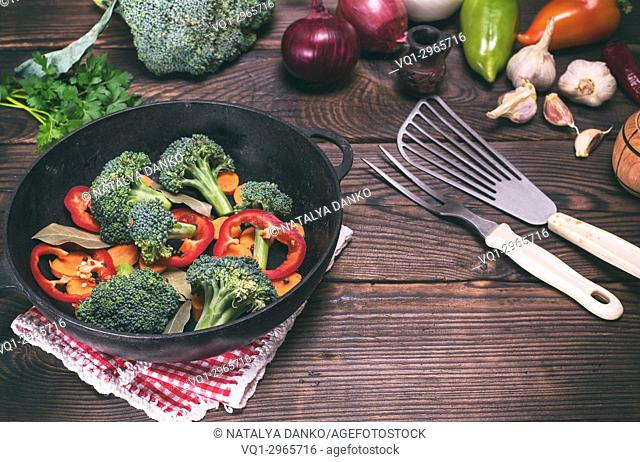 Fresh vegetables in a cast-iron black frying pan on a brown wooden background, vintage toning