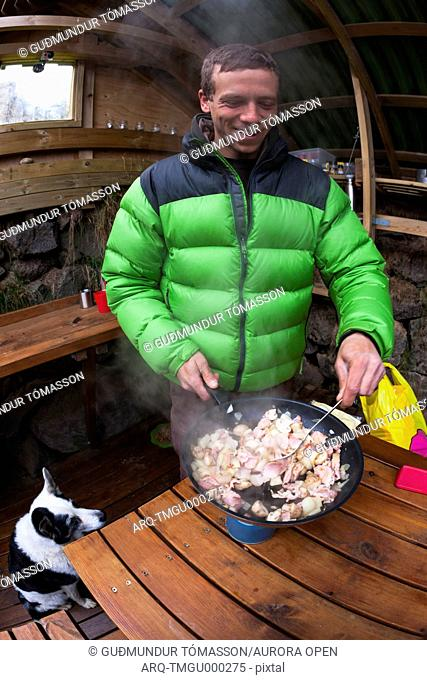Man cooking a stew in a shelter, made by climbers, located at Hnappavellir climbing area, southeast Iceland