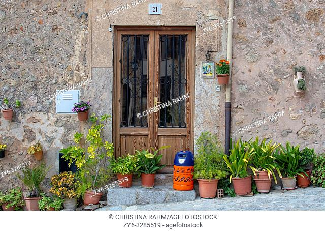 VALLDEMOSSA, MALLORCA, SPAIN - MARCH 21, 2019: Flowers and butane gas bottle outside door in the old town on March 21, 2019 in Valldemossa, Mallorca, Spain