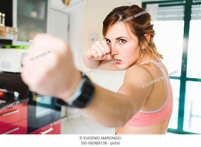 Young woman doing boxing training in kitchen