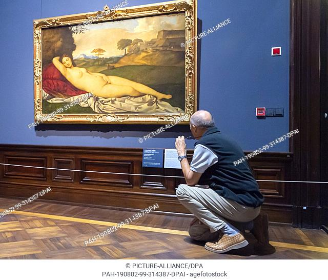 """02 August 2019, Saxony, Dresden: A visitor looks at the work """"""""Slumbering Venus"""""""" by Giorgione/Tizian in the exhibition """"""""Highlights of the Old Masters Picture..."""