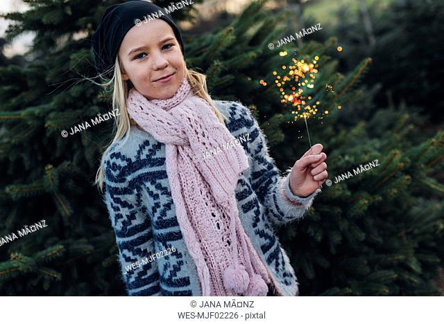 Girl holding sparkler in front of fir trees