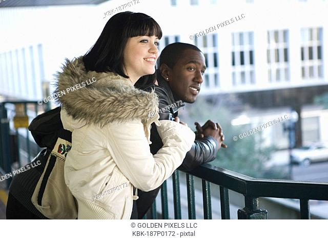Interracial couple leaning against railing overlooking city street