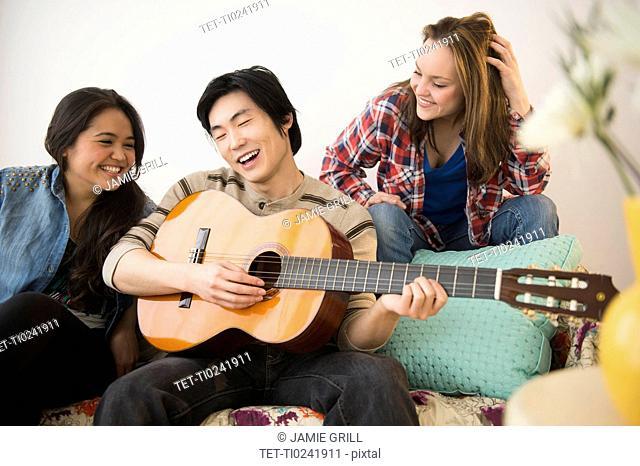 Young women listening to man playing guitar