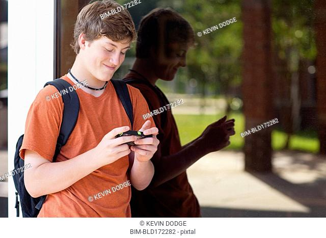 Caucasian teenage boy using cell phone