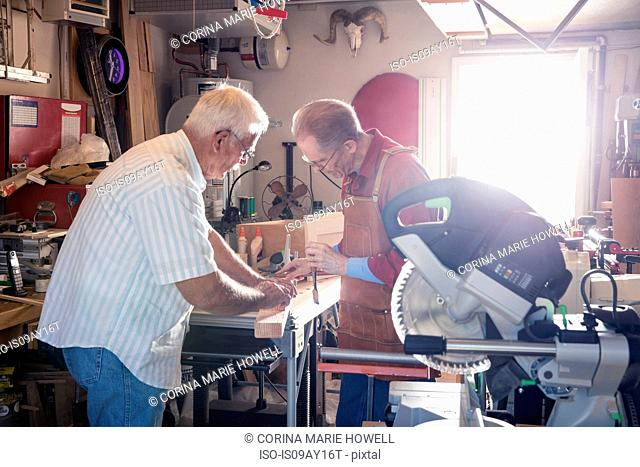 Senior men working with chisel in carpentry workshop