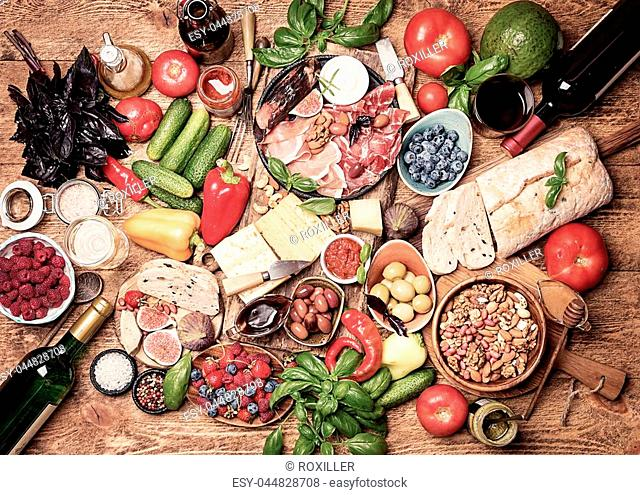 Top view table full of food. Italian antipasti wine snacks set. Cheese variety, nuts, Mediterranean olives, sauces, Prosciutto di Parma or jamon, tomatoes