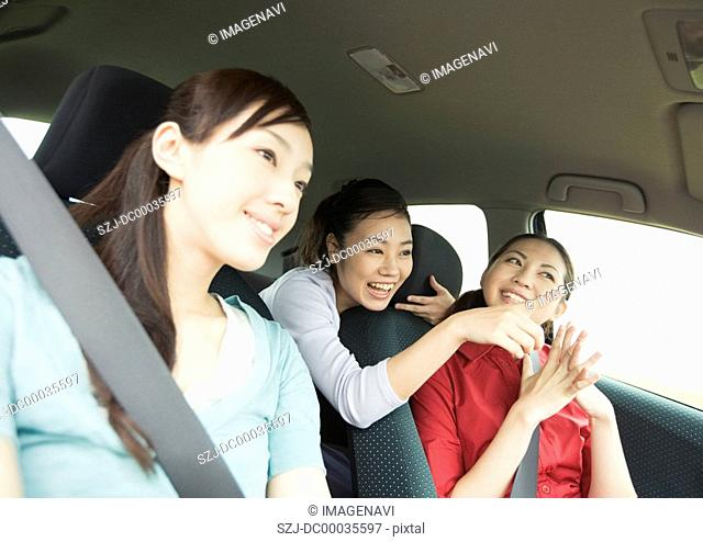 Three young women driving a car