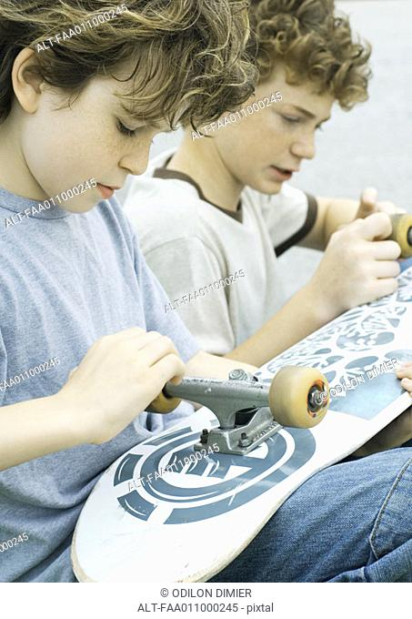Two boys looking at wheels of skateboard