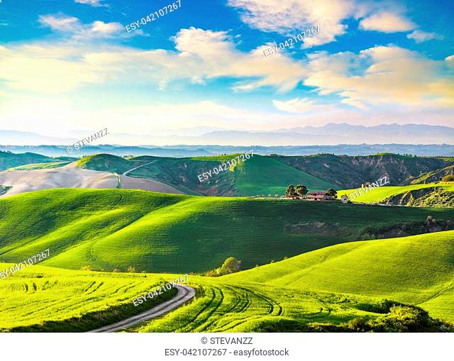 Tuscany, rural sunset landscape. Countryside farm, cypresses trees, green field, sun light and cloud. Volterra, Italy, Europe