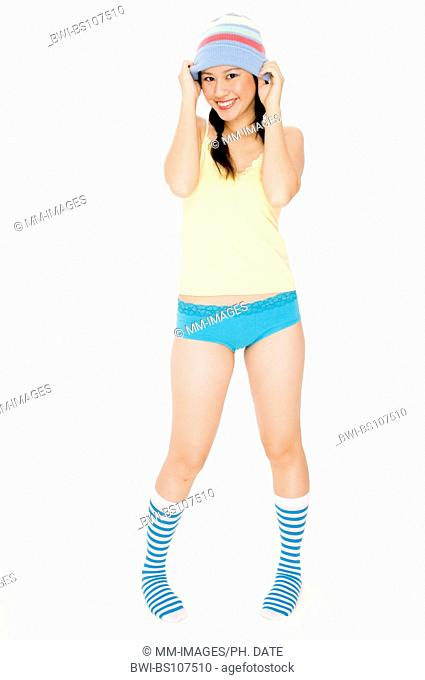 smiling young Asian woman in colorful underwear and a winter hat