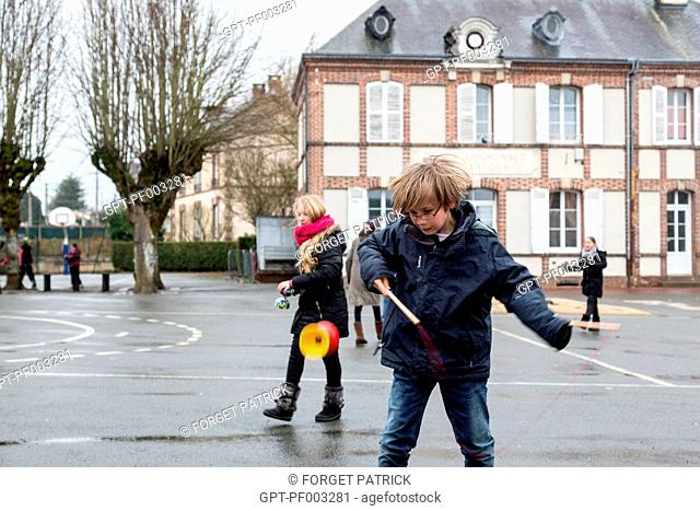 CHILDREN PLAYING WITH DIABOLOS IN THE SCHOOLYARD OF THE PRIMARY SCHOOL OF RUGLES (27), FRANCE