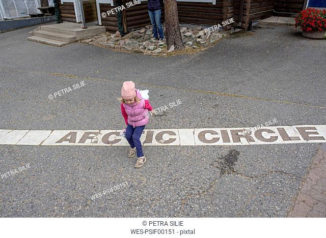Finland, Rovaniemi, Girl Crossing the Arctic Circle
