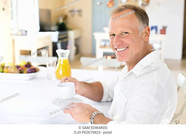 Portrait of smiling man drinking coffee at table