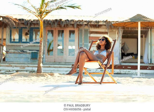 Serene young woman in bikini sunbathing on sunny beach