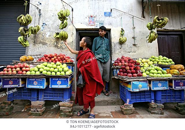 A young monk examines bananas for sale  Buddhist monks are living in monastries in and around Kathmandu  Many are illegal refugees from Tibet but live quietly...