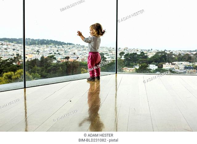 Curious Caucasian girl leaning on window admiring cityscape