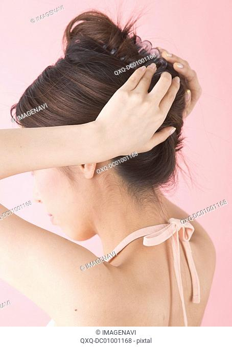 Rear view of woman pulling hair back