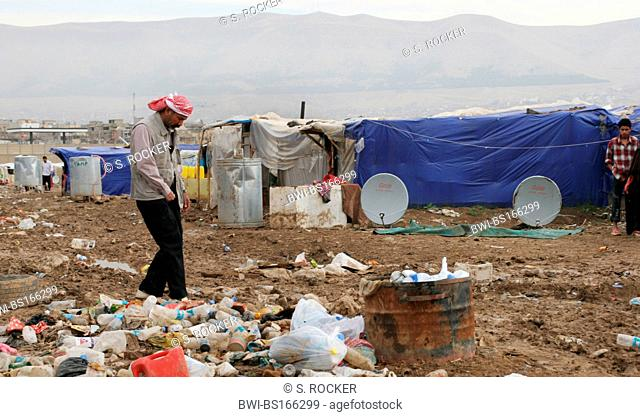 Arab refugee from Baghdad in camp in Sulaymaniyah steps through garbage and dirt, Iraq, Iraqi Kurdistan, Sulaimaniyya, Sulaymaniyah