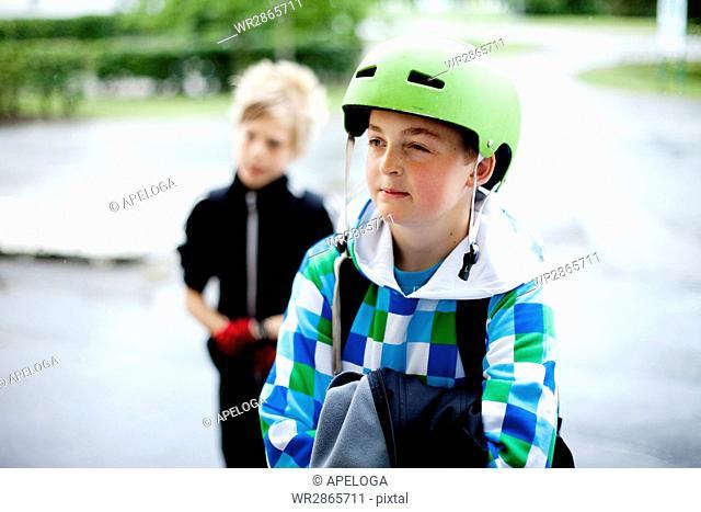 Boy wearing helmet with friend in schoolyard