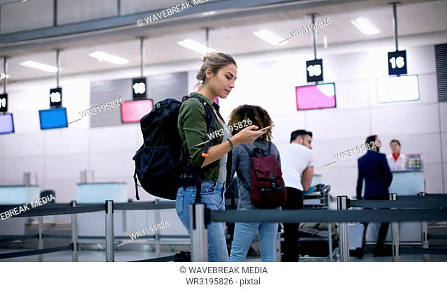 Woman using mobile phone while standing in queue