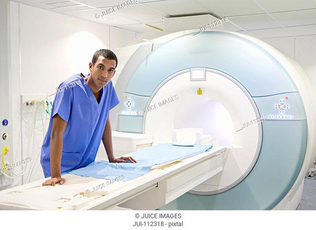 Portrait confident technician nurse leaning on MRI scanner in hospital