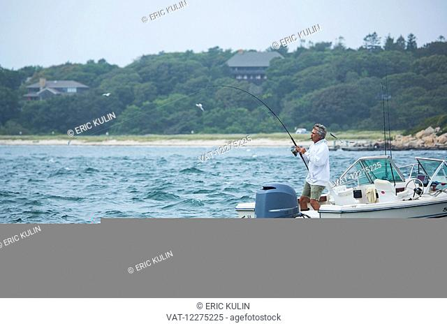 Man fishing from a boat; Cape Cod, Massachusetts, United States of America