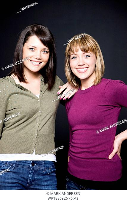 Two young women standing side by side