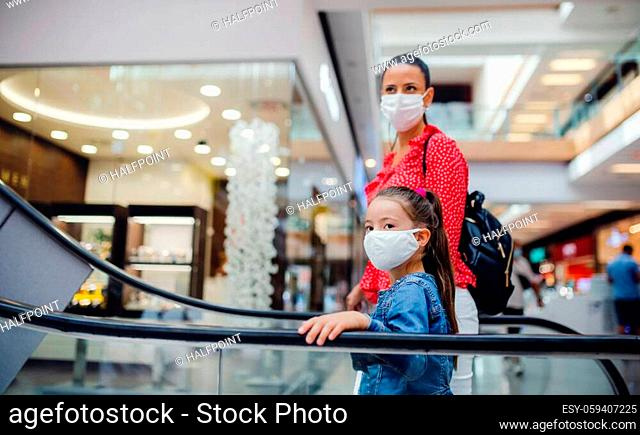 Young mother and daughter with face mask on escalator indoors in shopping center, coronavirus concept