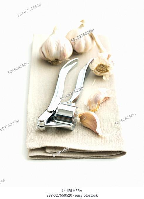 Garlic and garlic press on napkin isolated on white background