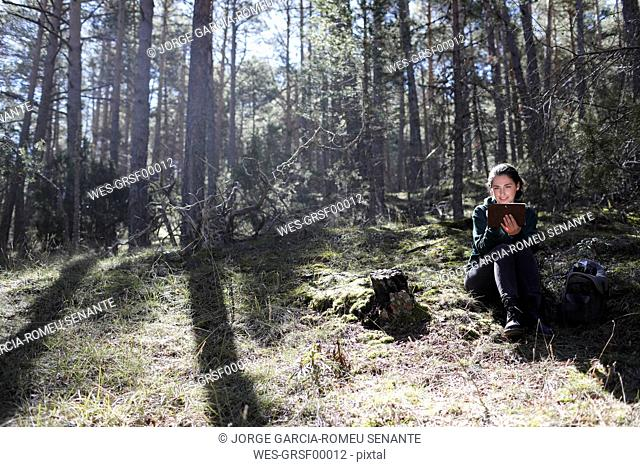 Young woman sitting in the forest, writing