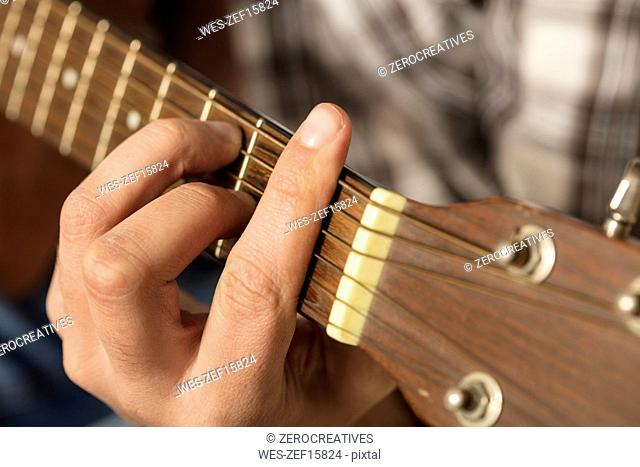 Close-up of man's hand playing guitar
