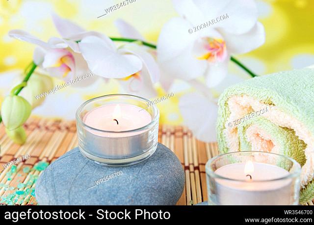 Spa concept: bath towels, two lighted candles on a wild rock and a branch of white orchid