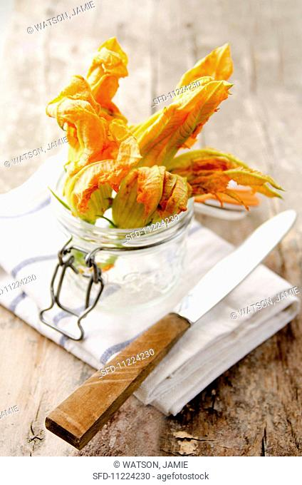 Courgette flowers in a storage jar on a tea towel with a knife