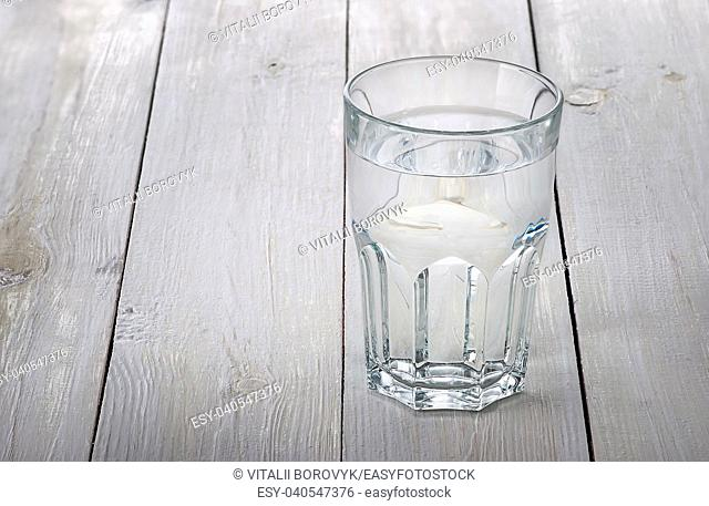 A glass of water on a white wooden table. Blurred background