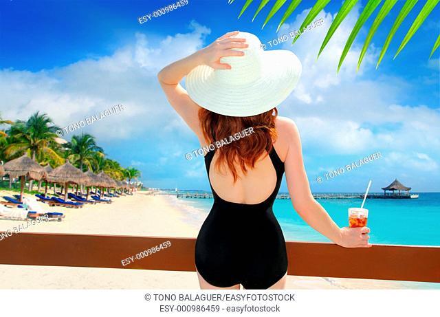 beach hat rear view woman cocktail tropical beach black swimsuit