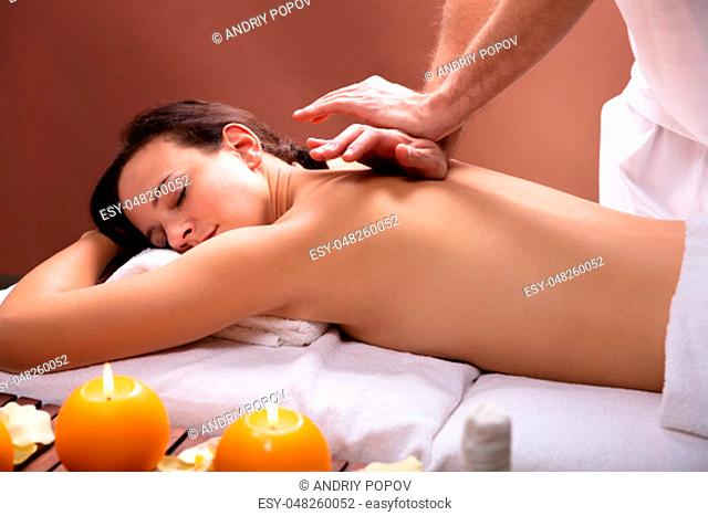 Therapist's Hand Giving Back Massage To Relaxed Young Woman In Spa